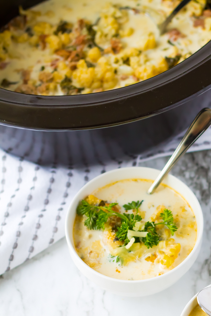 zuppa toscana soup in a bowl with slow cooker next to it
