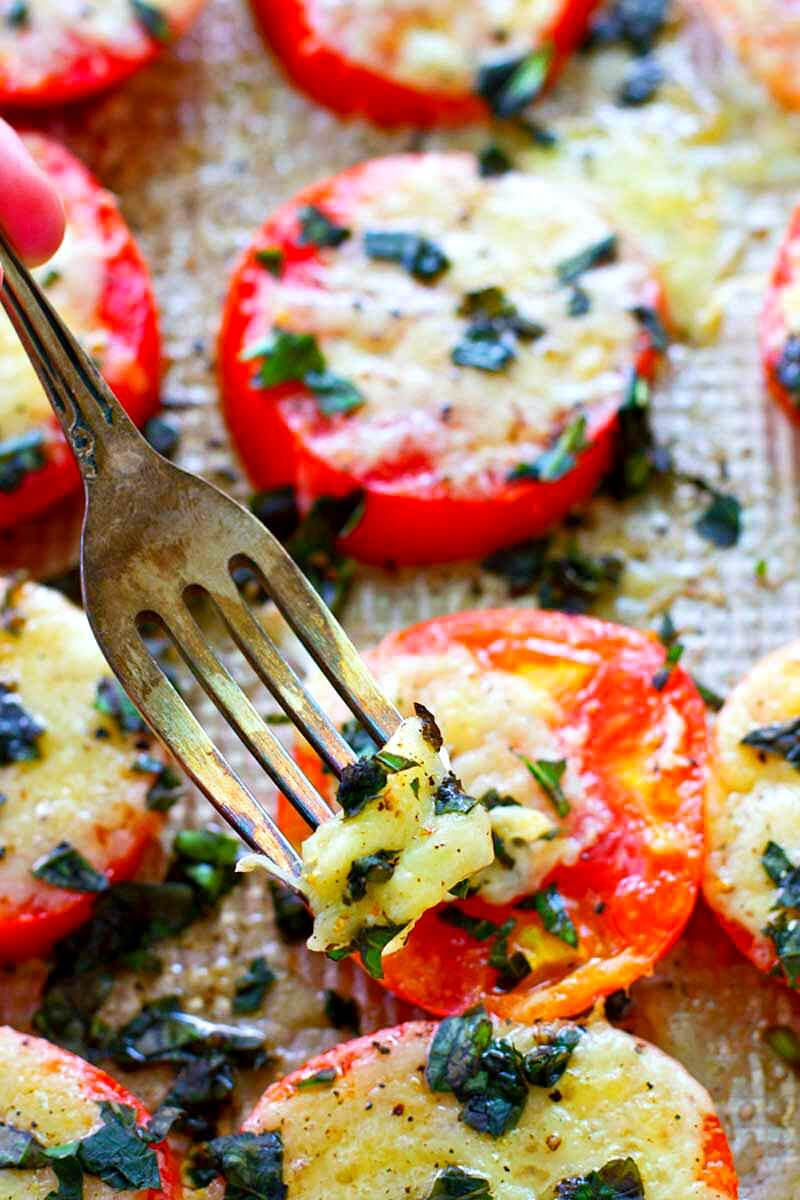These Baked Parmesan Basil Heirloom Tomatoes are covered in TONS of gooey cheese and fresh basil for one super-simple AND healthier summer side dish! You won't be able to resist eating them straight off the sheet.