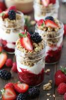 A breakfast parfait with a 3 berry compote, greek yogurt, granola, and chia