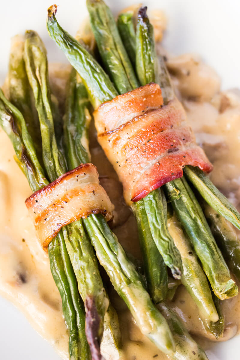 Bacon Wrapped Green Beans with Mushroom Gravy: Features tender green beans that are wrapped in bacon and baked atop a creamy delicious mushroom sauce. Umm good!