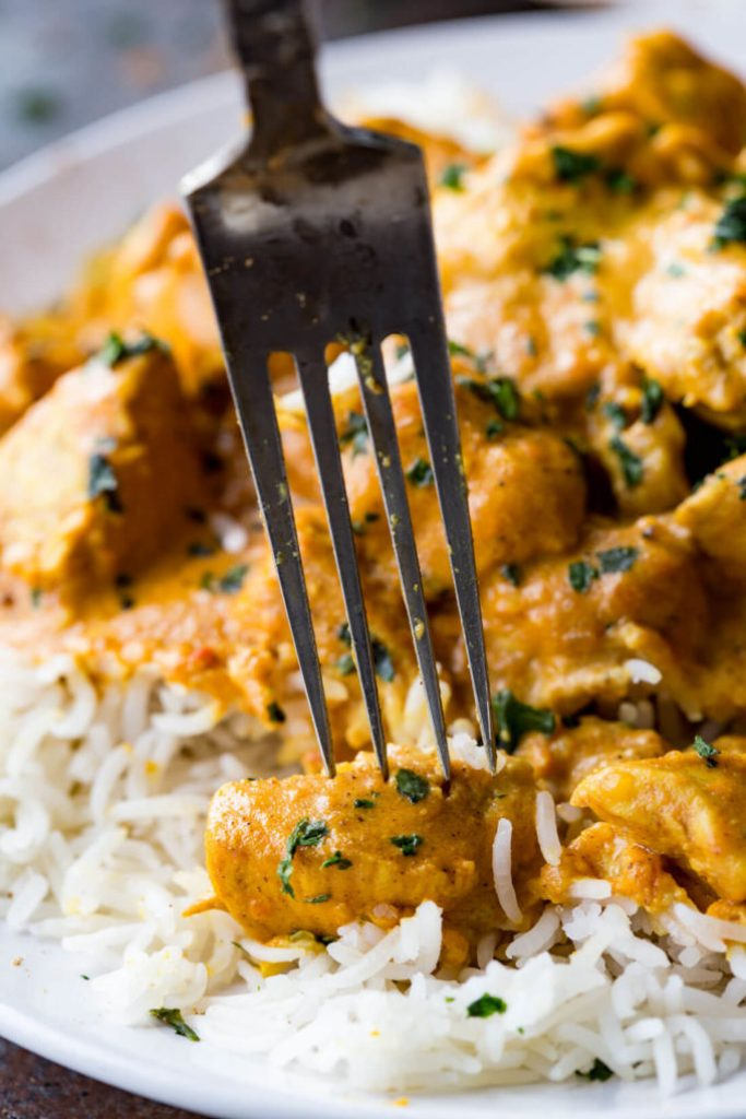 a fork with a piece of Indian butter chicken on it all over white rice