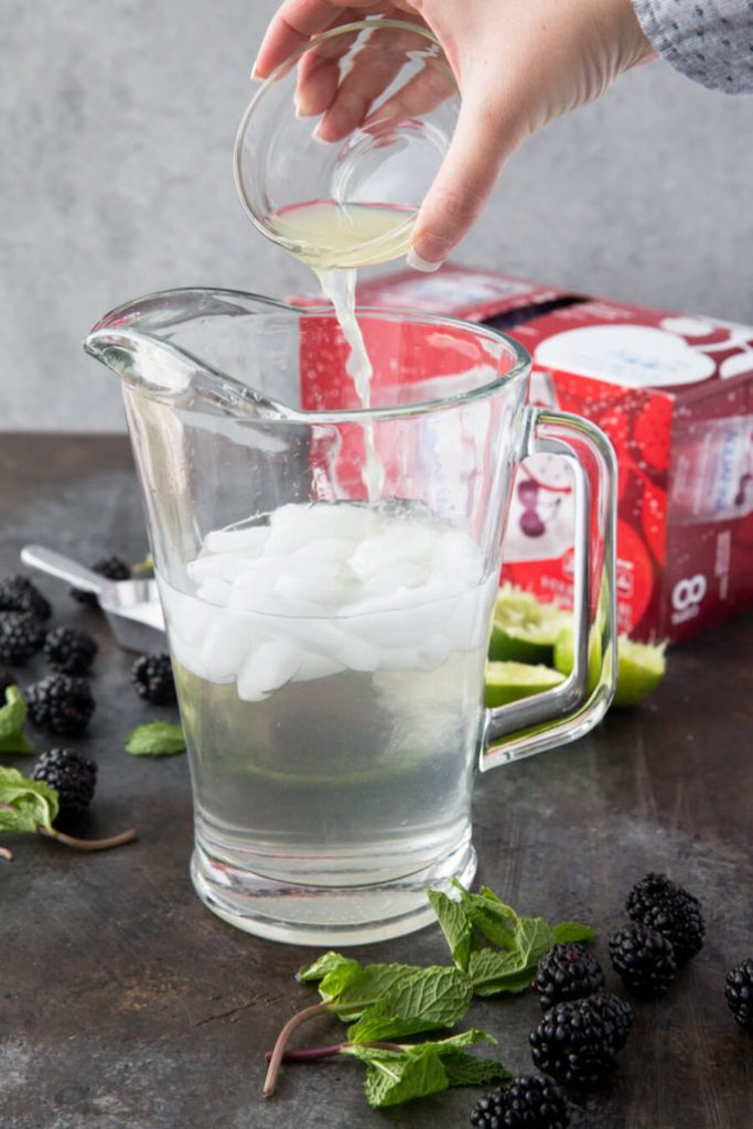 Pouring lime juice into a pitcher