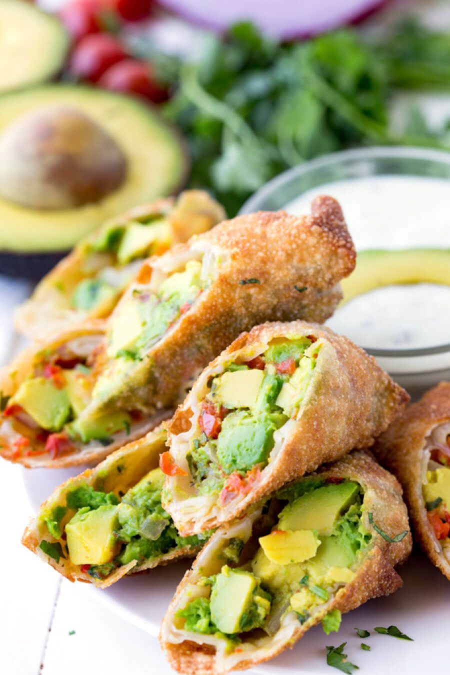 Avocado Egg Roll Dipping Sauce: Crunchy egg roll wrapper filled with chunks of California Avocados, cilantro, tomatoes, red onion, and roasted red peppers; dipped in a creamy avocado ranch dipping sauce!