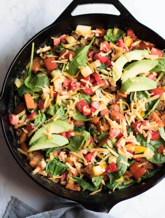 Southwestern sweet potato and ground beef skillet is loaded with fresh veggies and topped with cheese and avocado. A healthy, easy, and insanely delicious dinner that your whole family will love. Ready in 30 minutes!