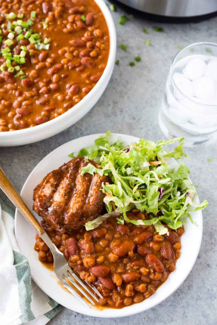 Summer staple, instant pot baked beans with a pork chop and green salad, on a white plate with a white bowl of beans
