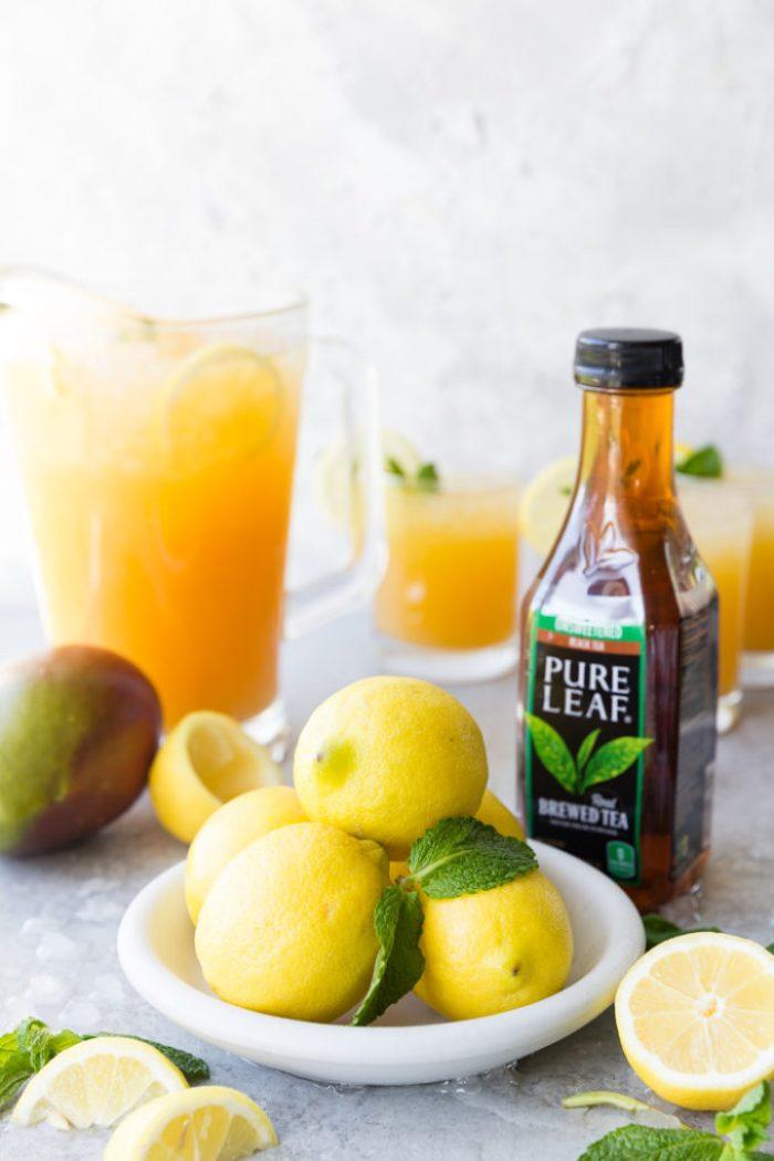 A white plate with lemons and mint, a bottle of pure leaf black tea, a mango, and a pitcher of Mango Black Tea Lemonade