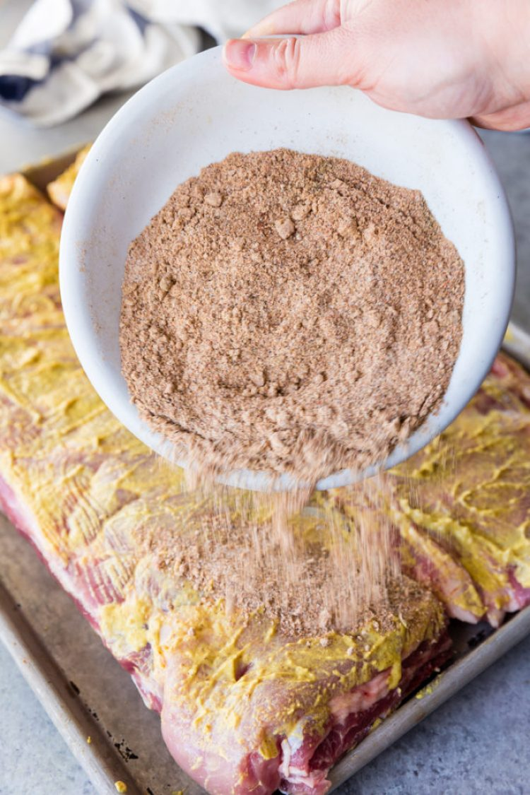 Pouring spice mixture on to ribs covered in mustard.