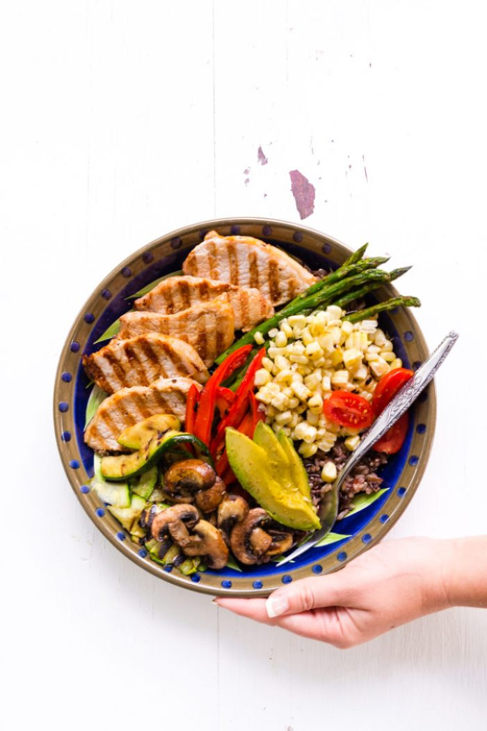 Grilled pork power bowl with grilled pork medallions, asparagus, avocado, red bell pepper, corn, mushrooms, and grape tomatoes