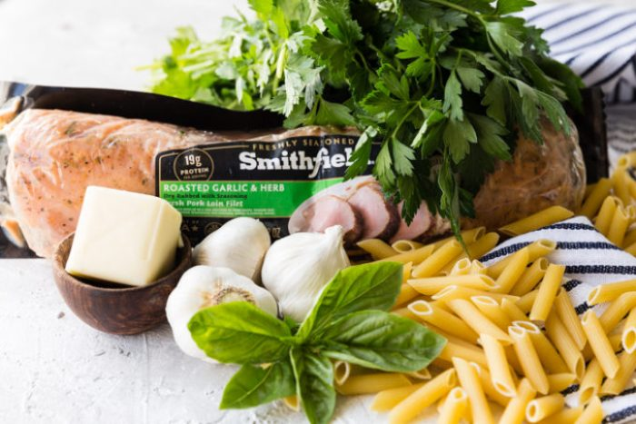 A package of Smithfield premartinated pork, penne pasta noodles, garlic, basil, parsley, and butter