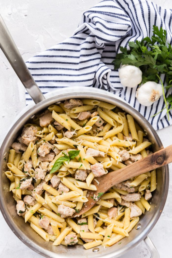 A skillet of roasted garlic and herb penne pasta with pork, on a blue and white striped napkin with garlic cloves and fresh herbs