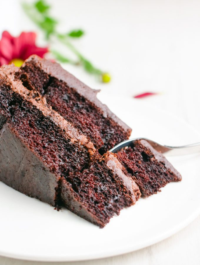 A slice of double layered chocolate cake with chocolate buttercream icing on a white plate.