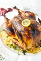 Roast Turkey - How to cook a turkey, a lovely roast turkey on a white platter with fresh herbs and sliced lemons