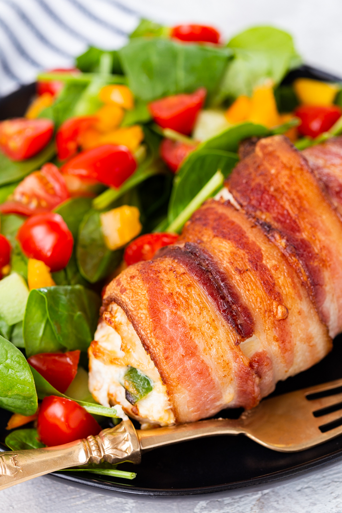 Air fryer jalapeno stuffed chicken breast keto low carb on a plate with a spinach salad