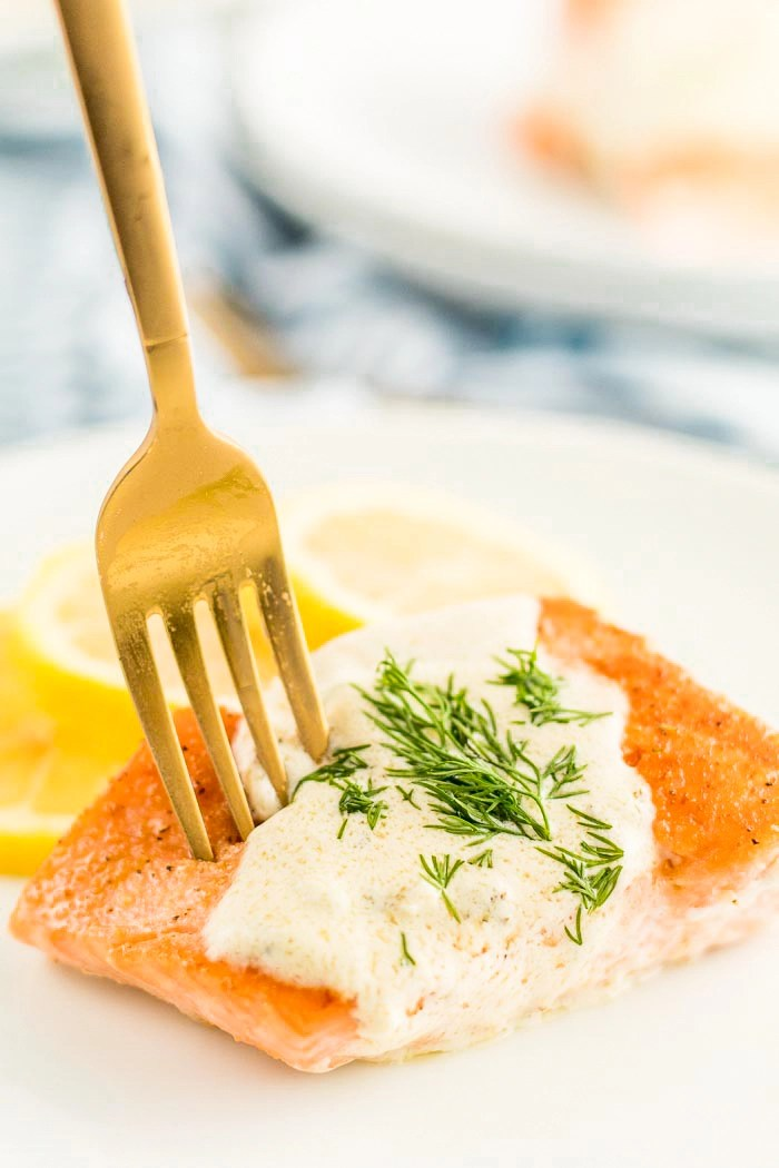 A white plate with creamy lemon dill sauce on salmon