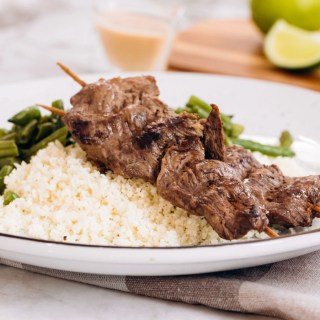 A white plate sitting on top of a checked napkin, topped with cauliflower rice, beef satay, and green beans