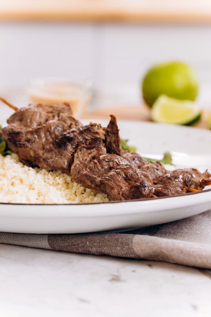 Low carb beef satay on a white plate with limes in the background