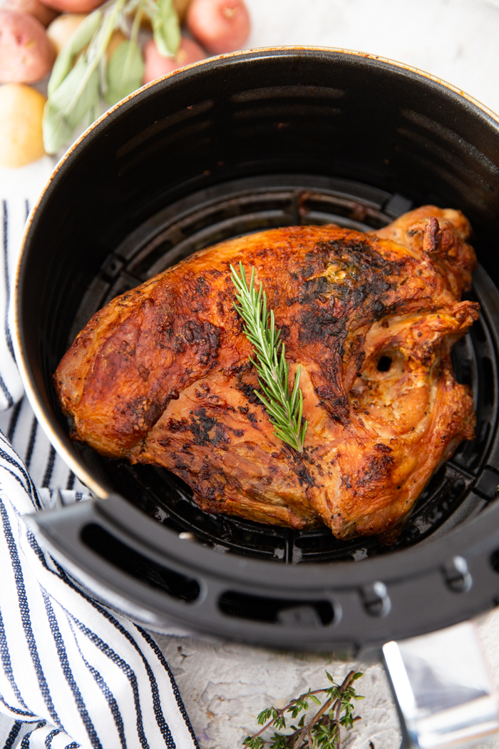 A full turkey breast cooked in the air fryer, topped with a sprig of rosemary