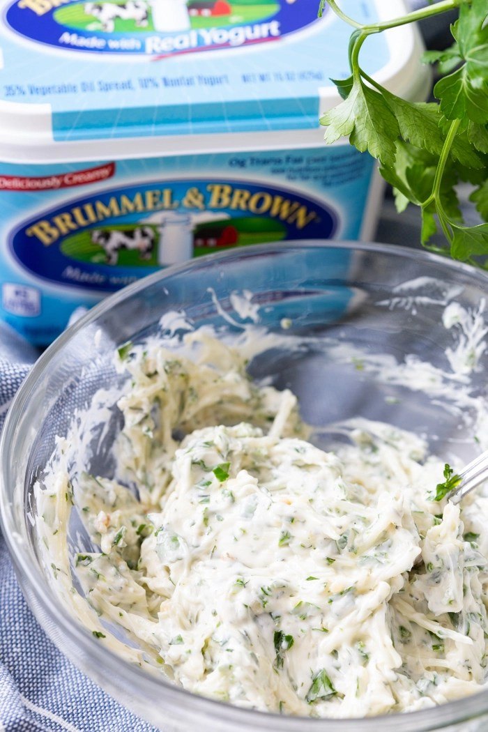 Garlic Parmesan Herb Spread in a clear glass bowl with parsley in the background