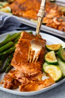 Cajun Butter baked salmon on a white plate with vegetables cooked on the same sheetpan