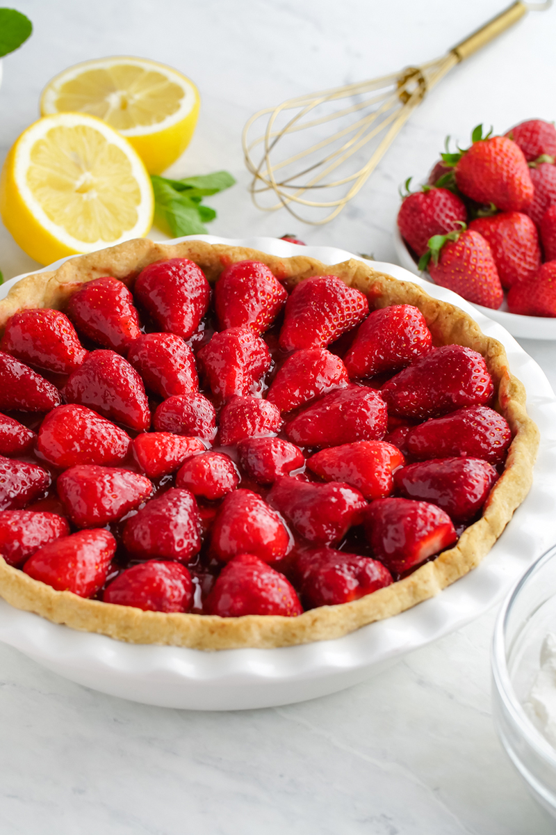 Fresh strawberry pie, a whole pie in a white pie plate with lemons and mint in the background