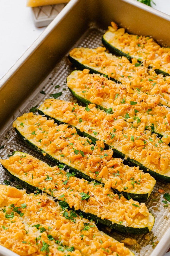 A baking tray with halved and cooked zucchini topped with crumb mixture.
