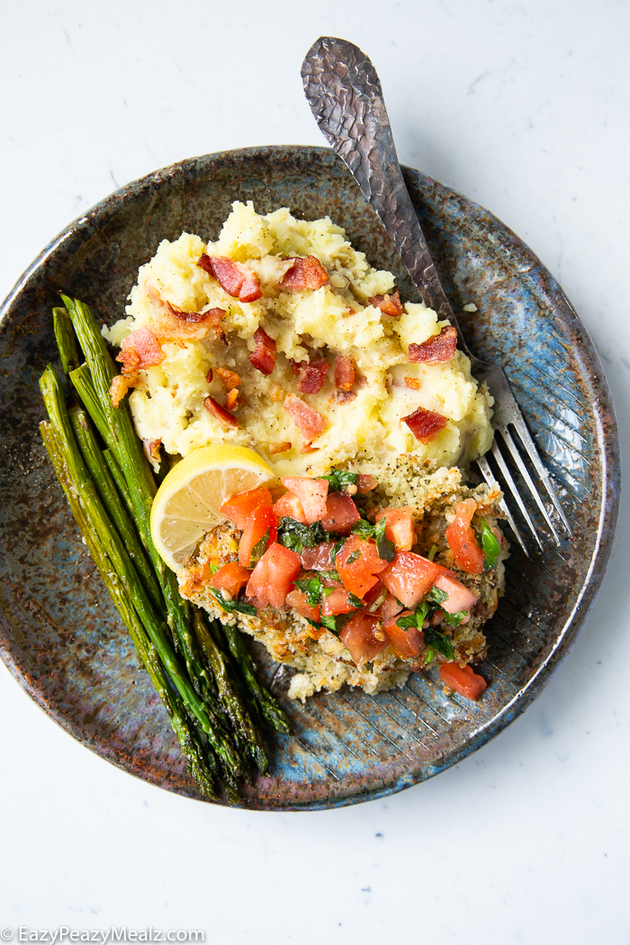 A plate with mashed potatoes, asparagus, and bruschetta chicken