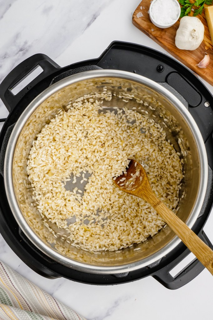 instant pot parmesan risotto in an instant pot with wooden spoon stirring