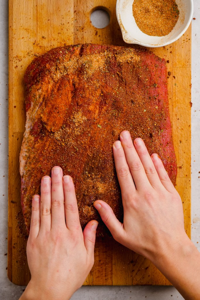 Coating beef brisket with spice mixture.