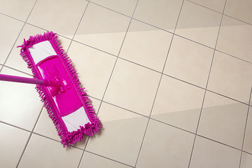 cleaning the tiled floor with purple mop