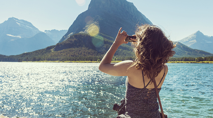 Woman Taking a Picture of a Mountain