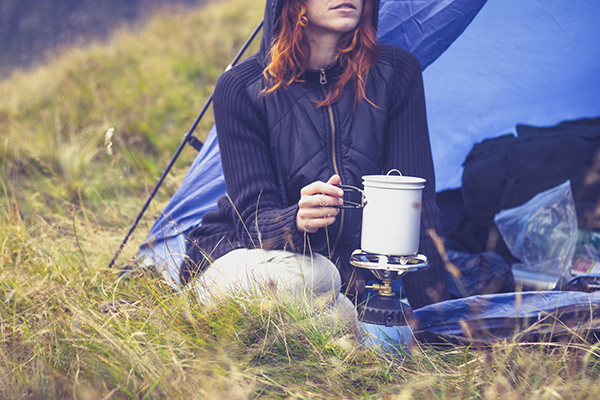 Woman camping and cooking with portable gas stove