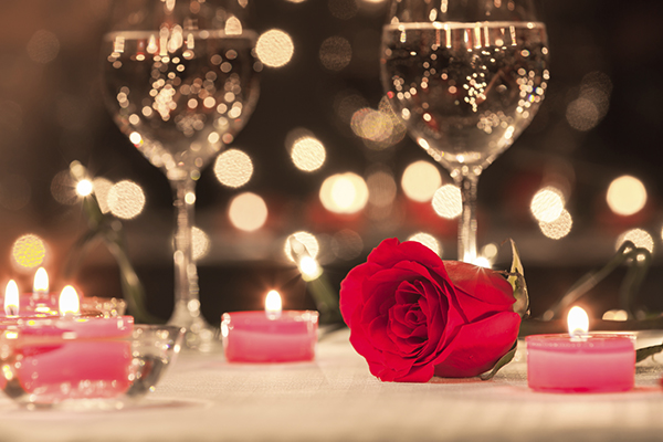 Two wine glasses and candles on dinner table