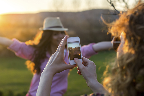 Woman taking photo with smartphone of friend outside
