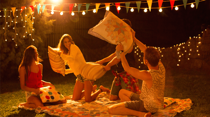 Young friends having a pillow fight in the backyard at night