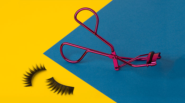 Eyelash curler and lashes on colorblock background