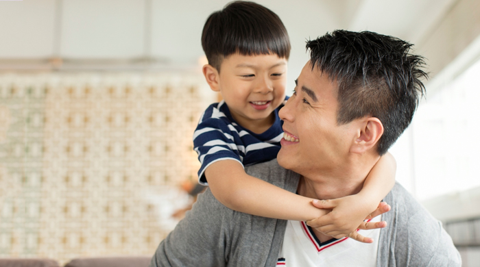 Little boy with his arms around his dad