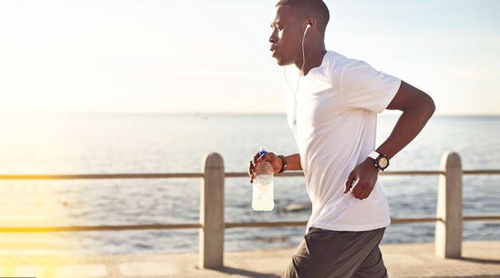 Man wearing white shirt and earbuds running