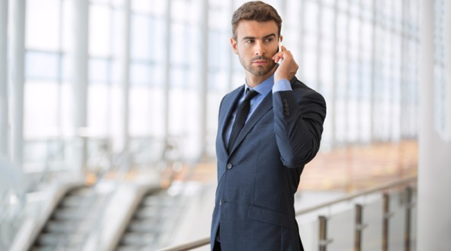 Man wearing a suit talking on a cell phone
