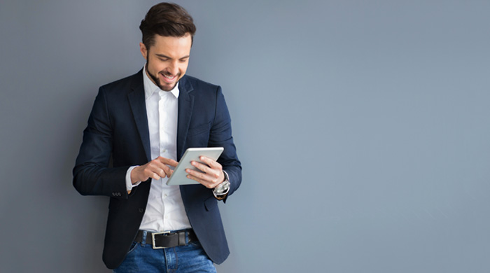Man wearing a blazer using a tablet