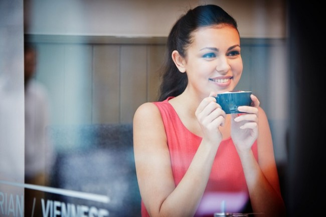 Young woman sitting in cafe with hot drink