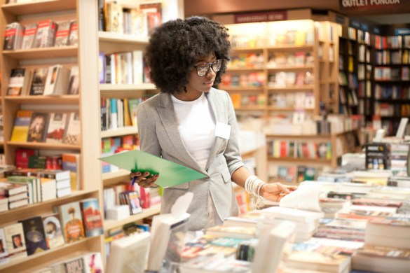 A woman with glasses working in a bookstore