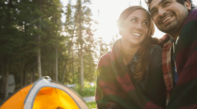 Young couple wrapped in blanket camping