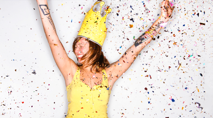 Woman wearing paper crown with confetti flying