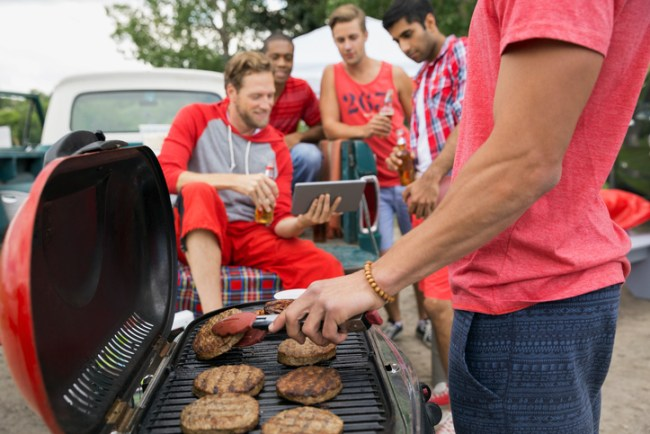 Man grilling at tailgate barbecue in field