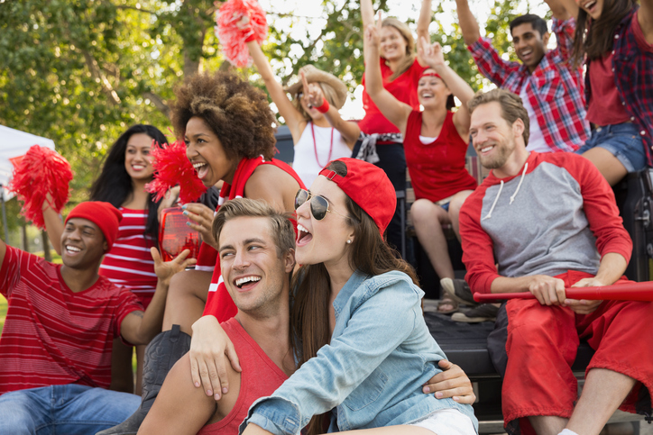 Friends cheering at tailgate barbecue in field