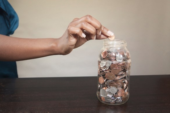 Woman putting coin into jar