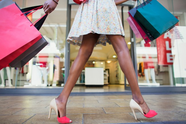 Shot of woman's legs, walking and carrying shopping bags