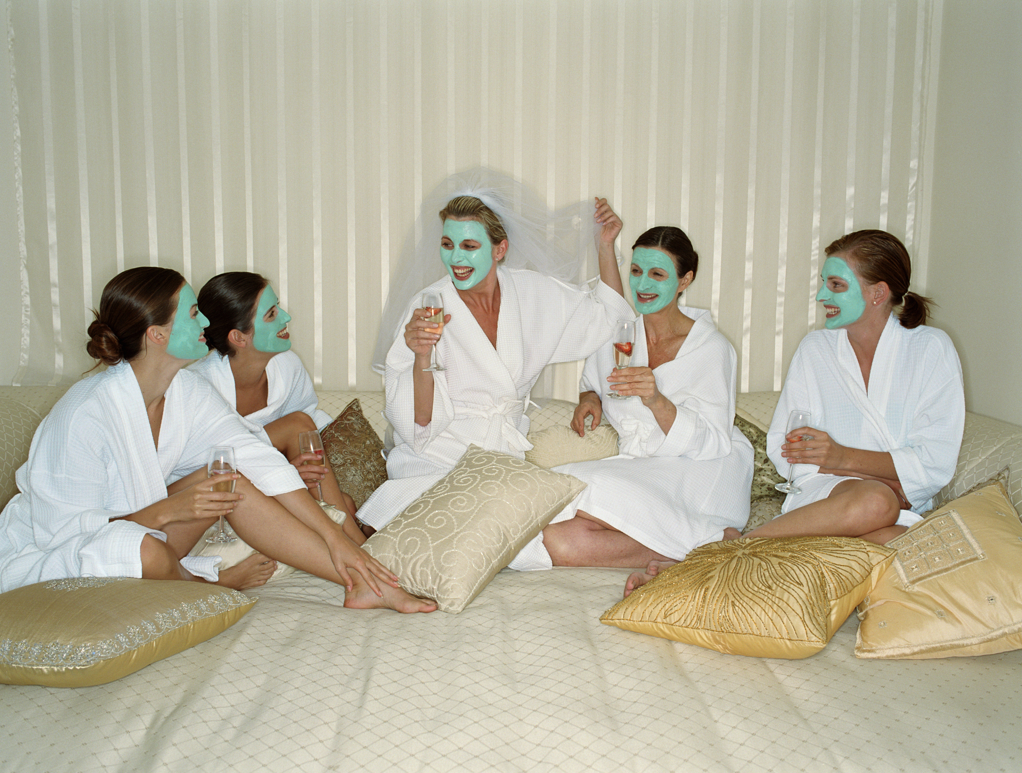 Five women in face masks holding champagne glasses, one wearing veil