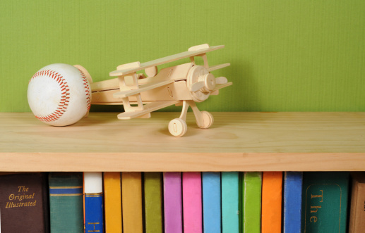 Wooden model airplane on top of book shelf