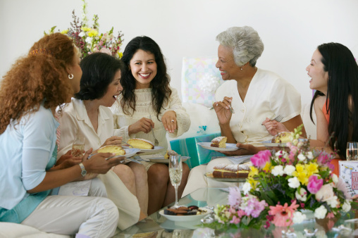 Women at gathering, smiling at woman wearing engagement ring